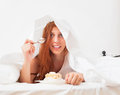 Long haired woman eating sweet cake in bed under white sheet at home Stock Image