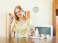 Long haired woman with medications at table in living room Stock Image