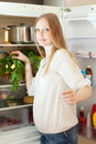 Long haired woman near opened refrigerator Lizenzfreie Stockfotos