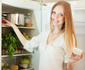 Long haired woman near refrigerator at home Stockbilder
