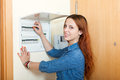 Long haired woman turning off the light switch at power control panel in home Stock Photo