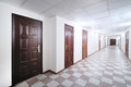 Long hallway with brown wooden doors grey and floor covered by tiles Stock Photos