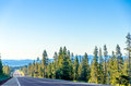 Long highway and forest scenic passing through a lush green with blue hills in the background near bend oregon Stock Image