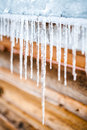 Long icicles melting of a roof top log wood chalet Royalty Free Stock Photography