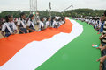 Long indian national flag being carried by school children assemble with to render anthem to mark th year of the song in event ntv Royalty Free Stock Photos