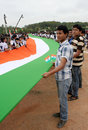 Long indian national flag being carried by school children assemble with to render anthem to mark th year of the song in event ntv Stock Photos