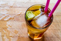Long island iced tea cocktail with lime, ice and served with pink straw Royalty Free Stock Photo