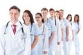 Long line of smiling doctors and nurses receding or queue in white uniforms wearing stethoscopes around their necks isolated on Stock Photo