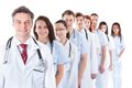Long line of smiling doctors and nurses receding or queue in white uniforms wearing stethoscopes around their necks isolated on Stock Photography