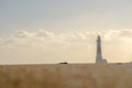 Long, low angle shot of lighthouse beyond bokeh effect sand Royalty Free Stock Photo