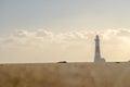Long, low angle shot of lighthouse beyond bokeh effect sand Royalty Free Stock Photo
