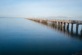 Long pier stretching out in the water with land horizon Royalty Free Stock Image