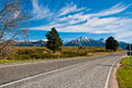 Long road stretching out to dry mountain range at lindis pass the highest highway in new zealand Royalty Free Stock Photo