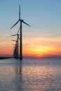 Long row of windturbines with sunset over the sea Royalty Free Stock Photo
