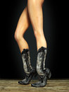 Long sexy female legs wearing cowboy boots Royalty Free Stock Photos
