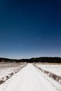 Long snowy road and clear starry sky in moon light see my other works portfolio Stock Image