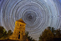 Long stars trails highlighting earth rotation around north star over ancient castle tower foreground Royalty Free Stock Images