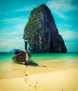 Long tail boat on beach thailand tropical with limestone rock krabi cross process vintage style Stock Photo