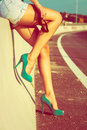 Long tan legs woman in high heel green shoes outdoor shot summer day Royalty Free Stock Image