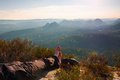 Long tired male legs in dark hiking trousers take a rest on peak of rock above valley Stock Images