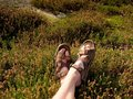 Long tired naked legs in hiking sandals on peak. Hiking in sandstone rocks, hilly landscape Royalty Free Stock Photo