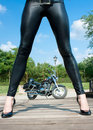 Long  woman`s  legs  with view on motorbike Royalty Free Stock Photo