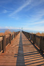 The long wooden pier on the lake kinneret shore of sunny spring day sunset Stock Photos