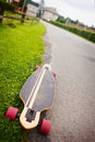 Longboarding longboard by the asphalt road at the border of a village Royalty Free Stock Image