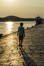 Lonley boy walking by the sea at sunset old stone pavement texture in croatia Stock Photography