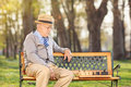 Lonley senior playing chess outdoors in park Royalty Free Stock Image