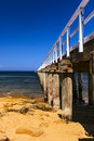 Lonsdale jetty striking image of the at point the is made of timber over golden sand and green sea under a blue sky point Royalty Free Stock Photography