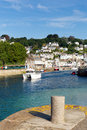 Looe harbour wall and boats in this beautiful cornish seaside town on river cornwall england with blue sea sky photographed from Stock Images