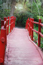A look down the path of red, wooden bridge at Magnolia Plantation and Gardens. Royalty Free Stock Photo