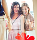 Look at that two beautiful women looking surprisedly something in the clothing store window Stock Photography