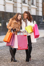 Look what i ve got full length of two beautiful young women che checking the shopping bags Royalty Free Stock Photos