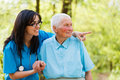 Look who are coming nurse pointing at arriving visitors to elderly lady Stock Photography