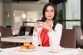 Looking away drinking coffee beautiful dark hair woman sitting at the restaurant Stock Image
