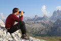 Looking through binoculars into valley in the mountains young man Royalty Free Stock Photography