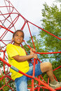 Looking boy holds and climbs on red ropes Royalty Free Stock Photo