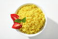Looking down at a bowl of yellow rice dish top view cooked served with greens and tomatoes in white ceramic Stock Images