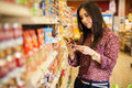 Looking at the food label cute young woman examining a product while shopping store Stock Photos