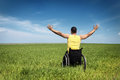 Looking for freedom happy handicapped man on a wheelchair over a green meadow Royalty Free Stock Images