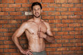 Looking good and feeling great cheerful young shirtless man holding thumb up smiling while standing against brick wall Royalty Free Stock Image