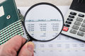 Looking numbers on printout with magnifying glass Royalty Free Stock Photo