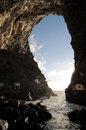 Looking out through a cave on volcanic island Stock Photo