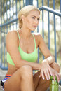 Looking out into the distance an attractive female athlete sitting and Royalty Free Stock Photos
