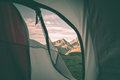 Looking out the mountain landscape at sunrise from interior of camping tent. Adventure traveling on the majestic European Alps, su Royalty Free Stock Photo