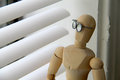 Looking out window on gloomy day wooden man with glasses a a overcast Stock Photo