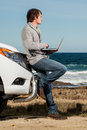 Looking out young handsome caucasian male leaning against a pickup truck with a laptop in his hands Stock Photography