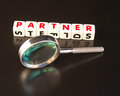 Looking for a partner text in red uppercase letters inscribed on white cubes next to hand magnifier dark surface Royalty Free Stock Photos